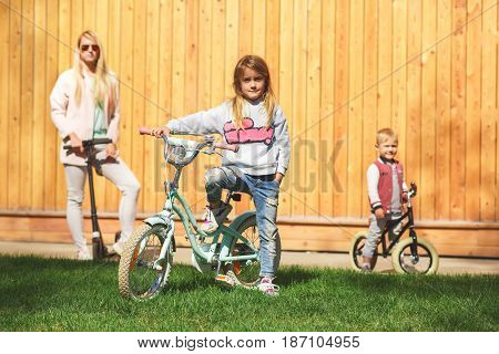 Mom with children on bicycles ride near wooden fence during day