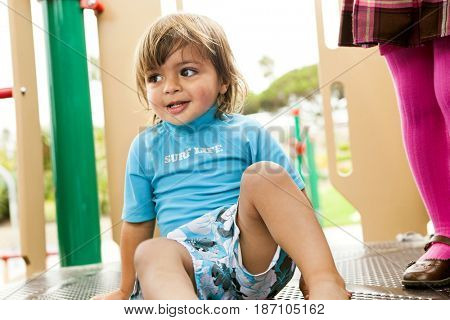 Mixed race boy on playground structure