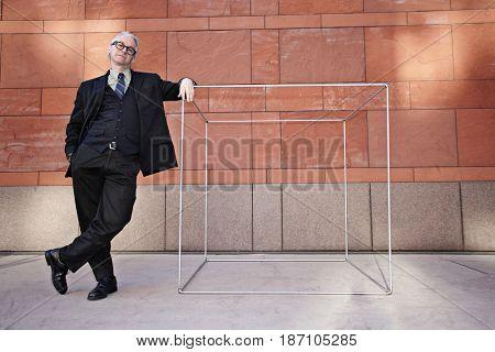 Caucasian businessman leaning on box on sidewalk