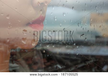 Working woman at the window in the rain.