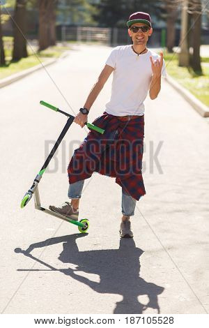 Man in baseball cap with scooter on road in park during day