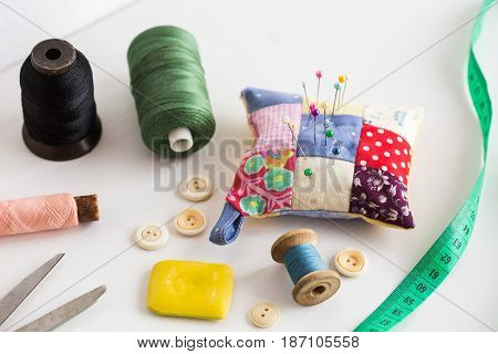 closeup sewing tools , patchwork, tailoring and fashion concept - thread spools, buttons, measuring tape, pincushion, scissors, pieces of colored patchwork fabric, soap on white desk