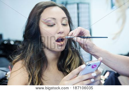 Mixed race woman with cell phone having make up put on