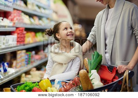 Little girl talking to her mother while visiting supermarket