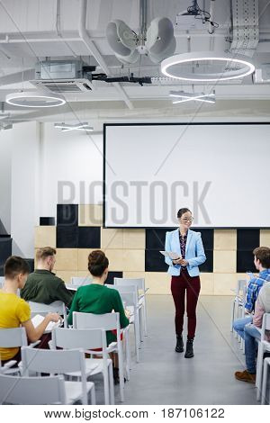 Young teacher making speech in front of audience in lecture hall