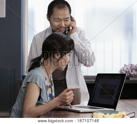 Japanese couple using laptop together