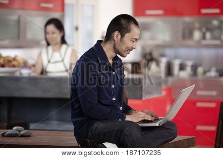 Japanese man using laptop in kitchen