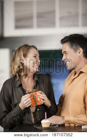 Caucasian man giving wife birthday gift