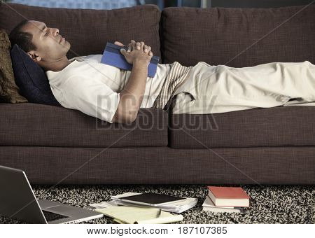 Mixed race man holding book and sleeping on sofa