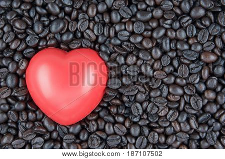 Red heart shape place on black roasted coffee beans use as texture or background.