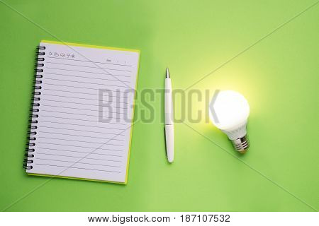 Note book and light bulb on green background.