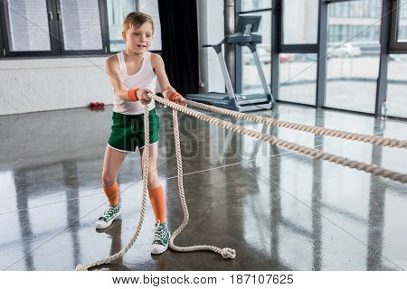 Adorable Kid Boy In Sportswear Training With Ropes At Fitness Studio, Children Sport Concept