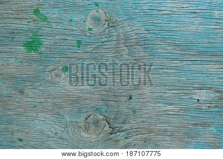 Old cracked wooden board with knots painted in light blue. Retro background - aged lumber surface. Weathered wood horizontal structure with place for text.