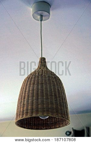 Gray, woven chandelier with a light bulb on the ceiling