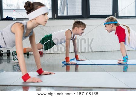 Cute Sporty Kids Exercising On Yoga Mats In Gym And Smiling, Children Sport School Concept