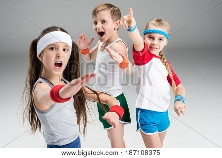 Group Of Sporty Children In Sportswear Exercising Together Isolated On Grey, Children Sport Concept