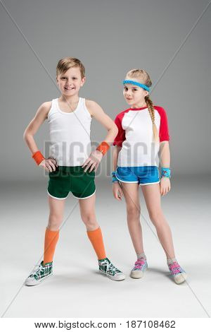 Full Length View Of Cute Smiling Boy And Girl In Sportswear Standing Together Isolated On Grey, Chil