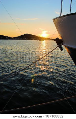 Prow of boat against sun setting at sea