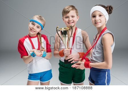 Smiling Boy And Girls With Medals And Champion Goblet Isolated On Grey