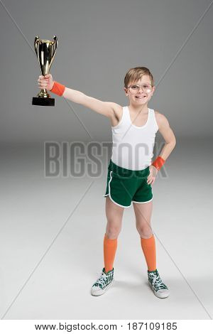 Smiling Boy Holding Champion's Goblet Isolated On Grey
