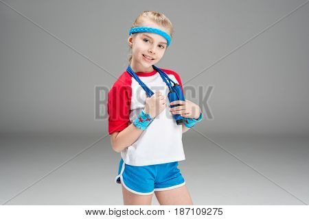 Portrait Of Smiling Girl In Sportswear Holding Skipping Rope Isolated On Grey