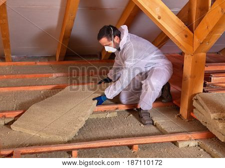 Man laying thermal insulation - placing rockwool panels to form layers
