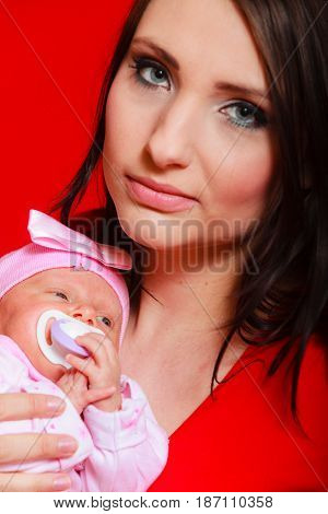 Family childhood and parenthood concept. Little newborn baby sleeping on mother chest. Red background