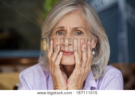 Close up portrait of worried senior woman sitting at table in cafe shop