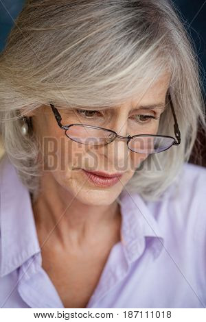 Close up of worried senior woman looking down