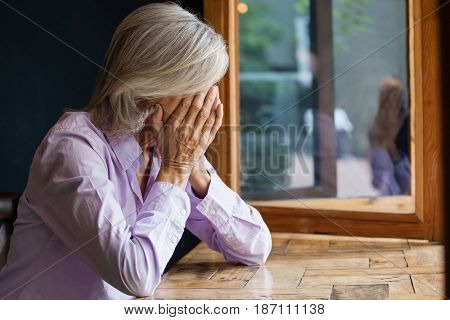 Close up of senior woman covering face while sitting at table in cafe