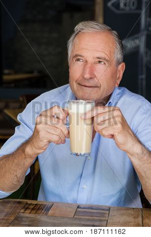 Senior man holding cold coffee while sitting at table in cafe shop