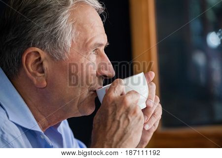 Close up of senior man drinking coffee at cafe shop