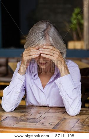 Thoughtful senior woman looking down while sitting at table in cafe shop