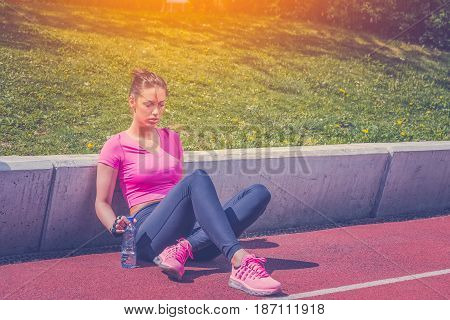 Fitness runner woman sitting on running track. Athlete girl taking a break during run to hydrate during hot summer day. Healthy active lifestyle.