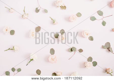 Flowers pattern texture made of beige roses eucalyptus branches on pale pastel pink background. Flat lay top view. Valentine's background. Floral texture background.
