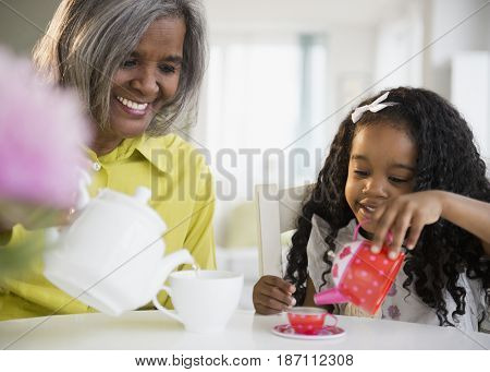 African American grandmother and granddaughter having tea party