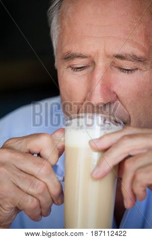 Close up of senior man drinking cold coffee at restaurant