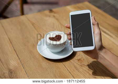Close up of woman photographing coffee cup on table at sidewalk cafe