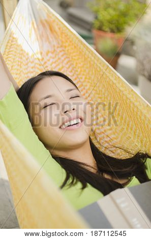 Asian woman napping in hammock