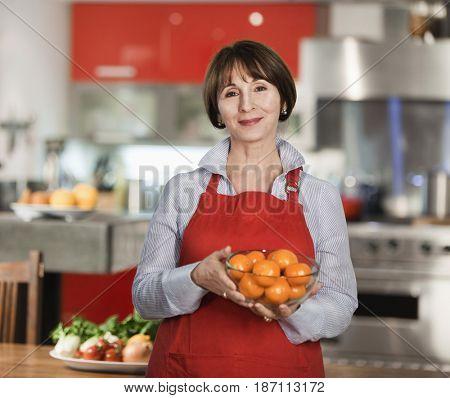 Caucasian woman holding bowl of oranges