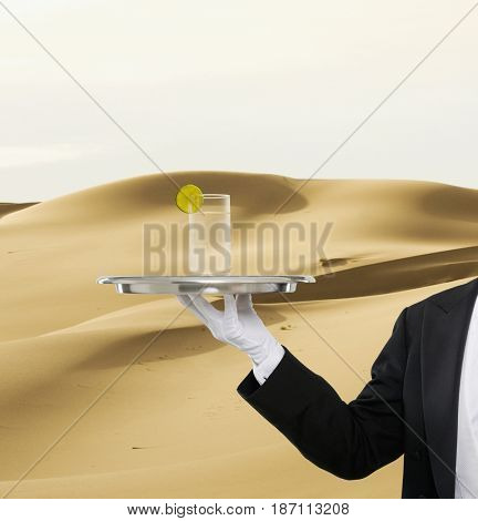 Caucasian butler holding water on tray in desert