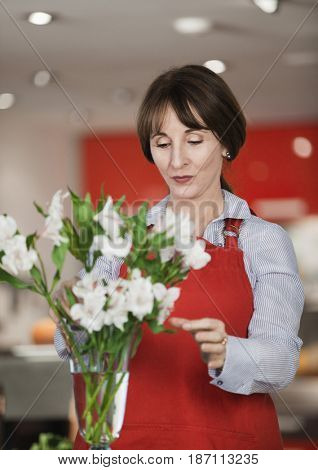 Caucasian woman arranging flowers in vase