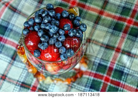 Fresh fruit in a glass of wine with brown beads on the checkered fabric