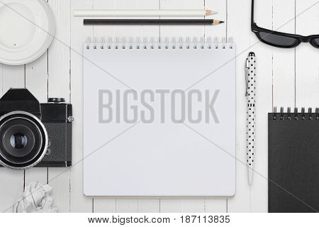 Monochrome Flat Lay Photographer Workspace On White Wooden Table. Top View.