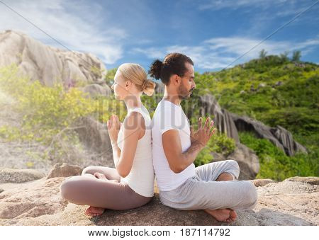 fitness, sport, people and yoga concept - smiling couple meditating in lotus pose sitting outdoors over natural background