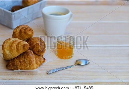 Cup of coffee small milk jug and croissants with peach jam on rustic wood table. Traditional French breakfast. Copy space.