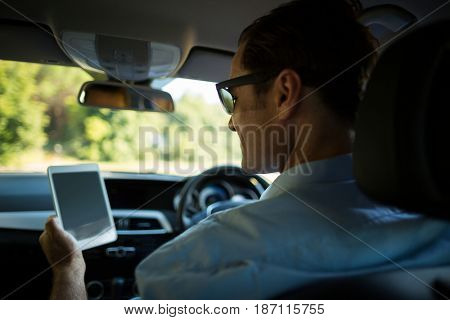 Rear view of man using digital tablet in car
