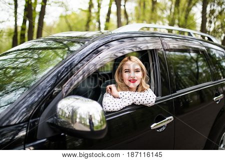 Young Woman Sitting In The New Car And Look From Window