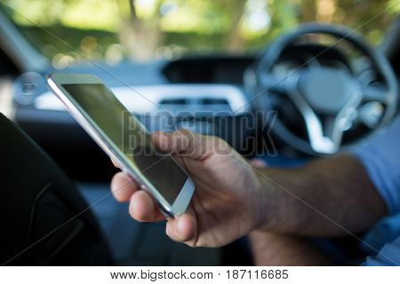 Mid section of man holding mobile phone