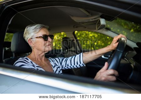 Confident senior woman driving car